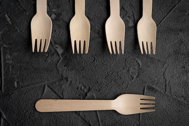 Coltello e forchetta di legno sui precedenti neri. concetto ecologico a rifiuti zero. vista dall'alto con spazio per il testo. copia spazio