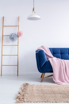 Scala in legno con due pompon in tulle e paralume bianco appeso sopra il divano blu navy