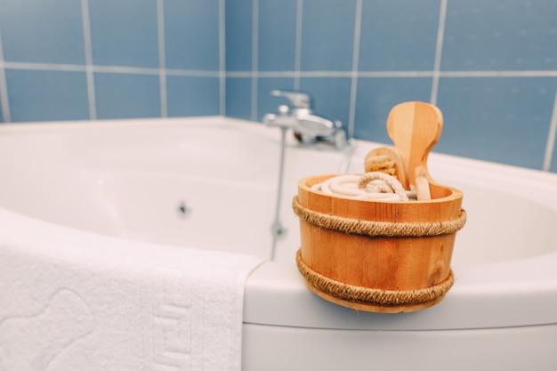 Mestolo in legno con accessori doccia sul bordo della vasca ad angolo vicino all'asciugamano in spugna