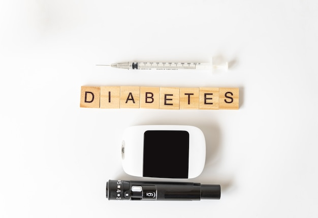 Diabete di parola di blocco di lettere in legno con lancetta, glucometro e siringa da insulina su bianco.