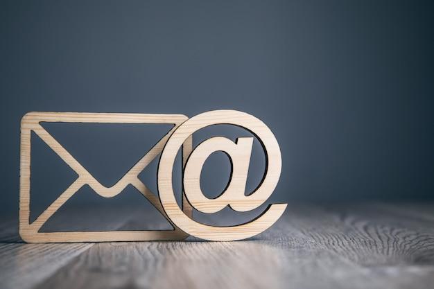 Lettera in legno con segno di posta elettronica su sfondo di legno