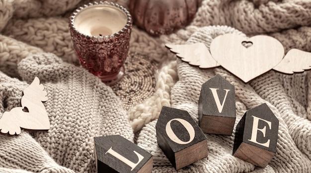 Lettere in legno compongono la parola amore su uno sfondo di articoli a maglia accoglienti. concetto di vacanza di san valentino.