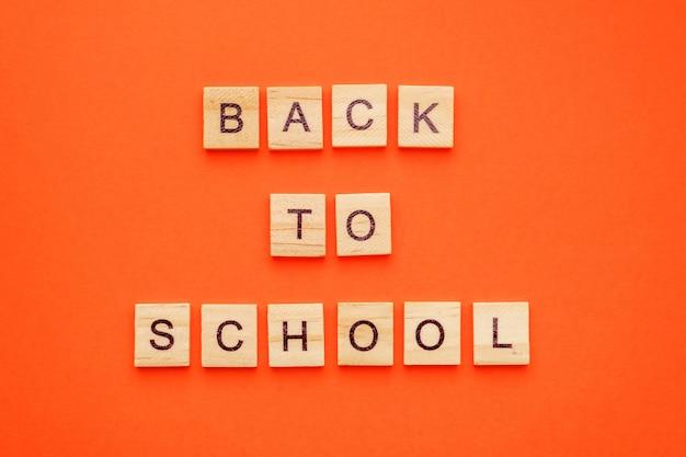 Lettere di legno con la frase di nuovo a scuola sull'arancia