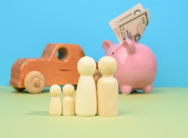 Famiglia di piccoli uomini in legno si trova sullo sfondo del maiale salvadanaio e auto in legno, concetto di risparmio di denaro