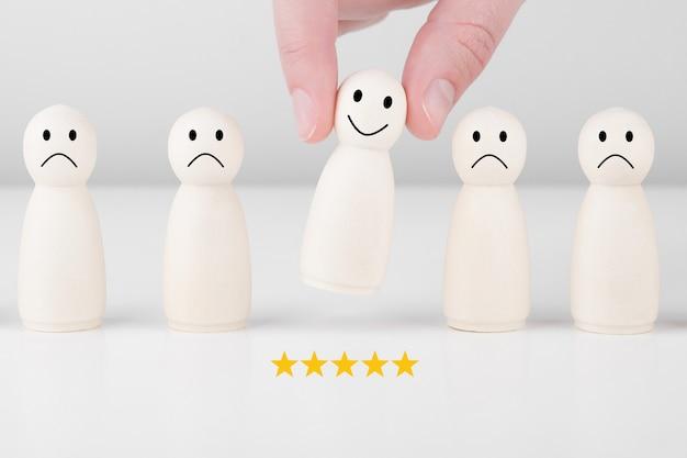 L'uomo di legno dà una valutazione a 5 stelle e una faccina sorridente. concetto di servizio al cliente e sondaggio sulla soddisfazione.