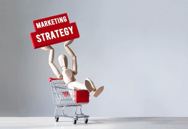 L'uomo di legno tiene un blocco di legno con la parola strategia di marketing, concetto