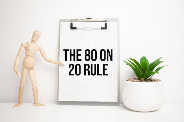 L'uomo di legno mostra con una mano alla lavagna bianca con il testo la regola 80 su 20