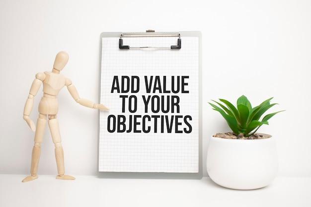 L'uomo di legno mostra con una mano alla lavagna bianca con il testo aggiunge valore ai tuoi obiettivi