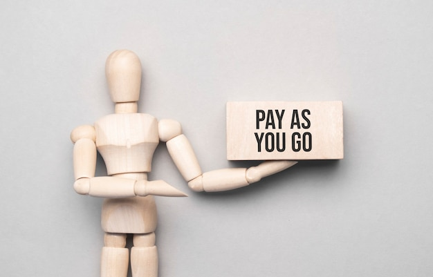 L'uomo di legno mostra con una mano al bordo bianco con il testo pay as you go
