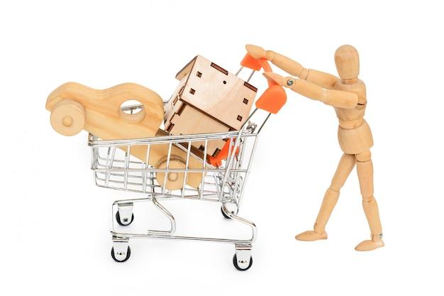Il manichino di legno trasporta un carrello con l'automobile e la casa di legno isolate su bianco. assicurazione di proprietà di ipoteca comprare concetto di affitto di vendita di acquisto della casa di sogno