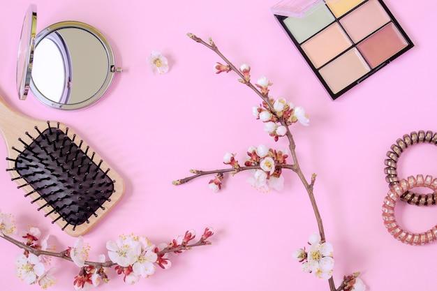 Pettine da massaggio in legno, spirali per capelli, piccolo specchio rotondo, tavolozza di correttori e rami di albicocca in fiore su sfondo rosa. concetto di bellezza femminile. cura dei capelli e del corpo a casa.