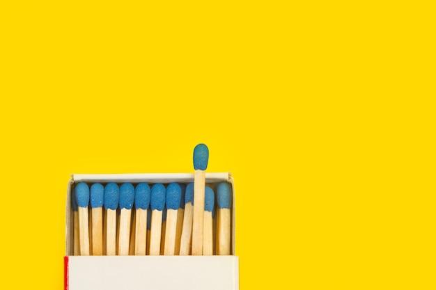 Fiammiferi in legno con testa blu in una scatola di fiammiferi isaolated