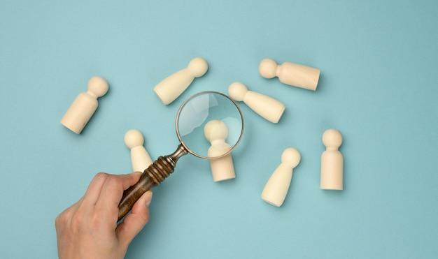 Uomini di legno e una lente di ingrandimento su sfondo blu. concetto di reclutamento, ricerca di dipendenti di talento e capaci, crescita della carriera, disposizione piatta
