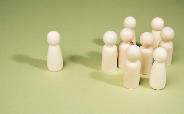 Uomini di legno stanno in un gruppo vicino a uno su uno sfondo verde, concetto di leadership, bulling