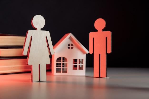 Modello in legno di famiglia e casa su un tavolo divorzio e concetto di divisione