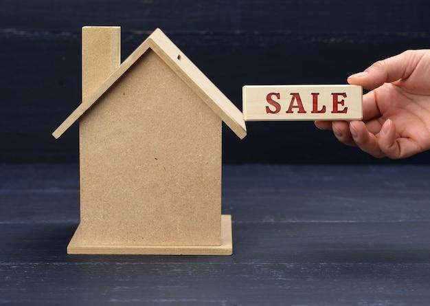 Il modello in legno di una casa e una mano tiene un blocco con un'iscrizione in vendita su una superficie blu