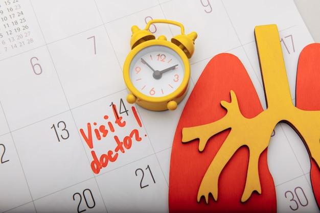 Modello in legno di polmone sul calendario con segno e primo piano sveglia gialla. assistenza sanitaria e concetto di diagnosi precoce.