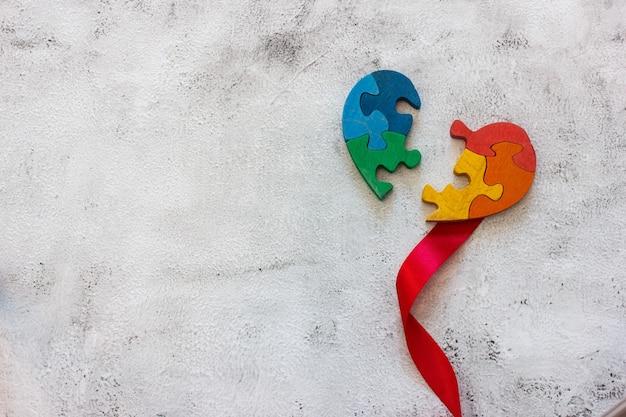 Puzzle multicolore in legno a forma di cuore spezzato su sfondo grigio. nastro rosso. concetto valentines day, relazione. spazio per il testo
