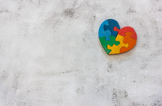 Puzzle multicolore in legno a forma di cuore su sfondo grigio. concetto valentines day, relazione. spazio per il testo