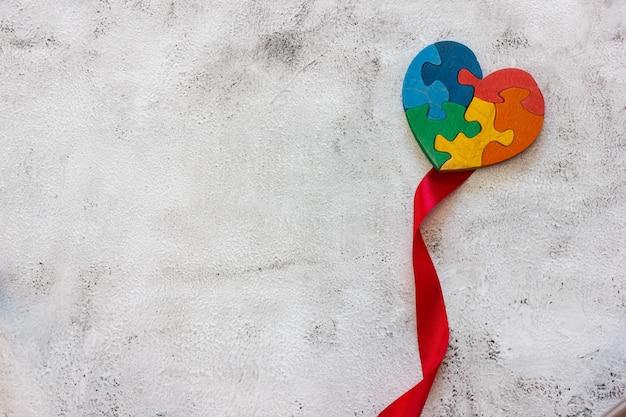 Puzzle multicolore in legno a forma di cuore su sfondo grigio. nastro rosso. concetto valentines day, relazione. spazio per il testo