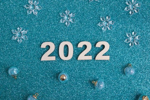 Numeri in legno capodanno 2022 con decorazioni natalizie su sfondo blu glitter
