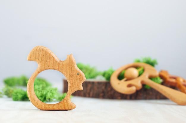 Scoiattolo giocattolo massaggiagengive bambino organico in legno su sfondo chiaro