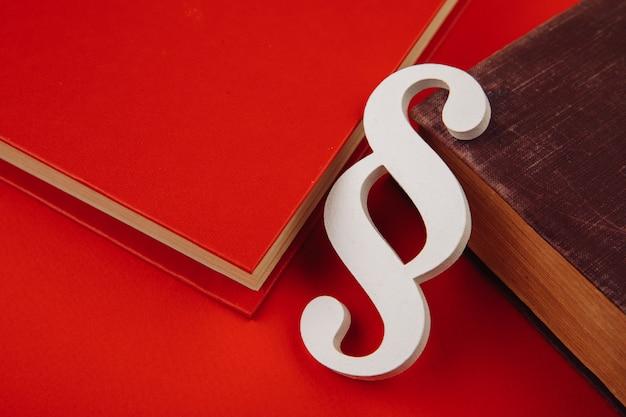 Simbolo di paragrafo in legno con libri su sfondo rosso.