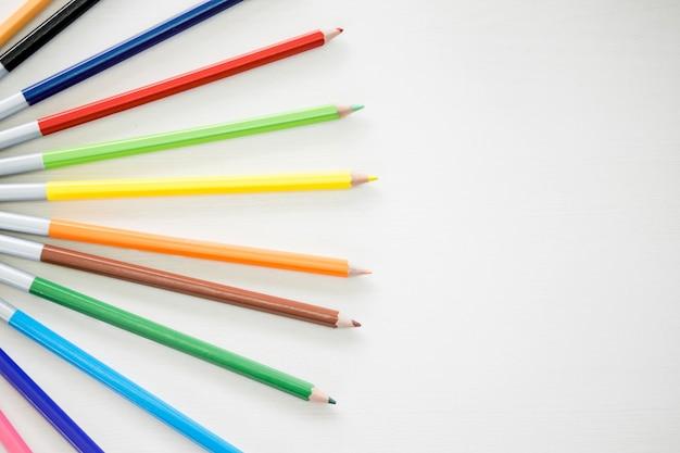 I colori della matita di legno stanno mettendo sul tavolo bianco di legno.