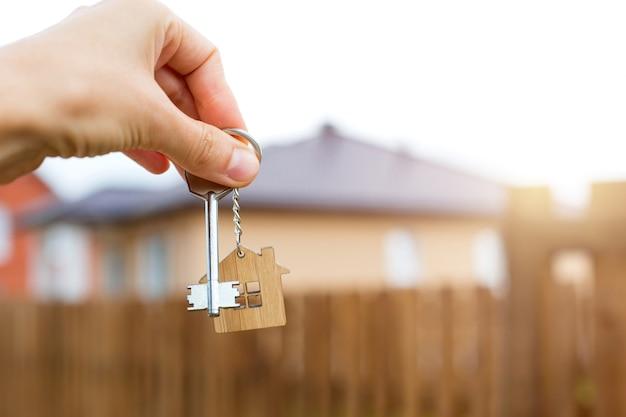 Ciondolo in legno di una casa e chiave in mano