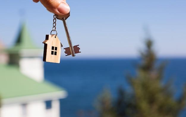 Pendente in legno di una casa e chiave. casa e vita sull'oceano, costruzione, progetto, trasferimento in una nuova casa, mutuo, affitto e acquisto di immobili. copia spazio