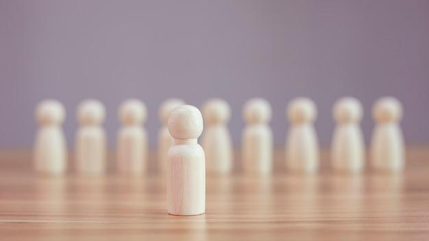 Modello di persona in legno tra persone sfocate su sfondo nero concetto di leadership