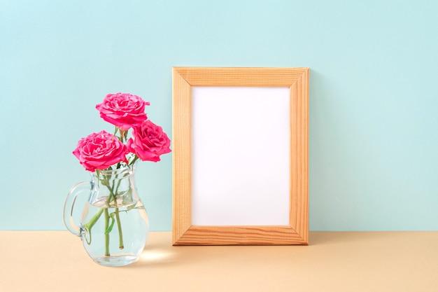 Cornice per foto in legno e bouquet di rose rosa in vaso di vetro su sfondo pastello. mock up con elementi decorativi. copia spazio