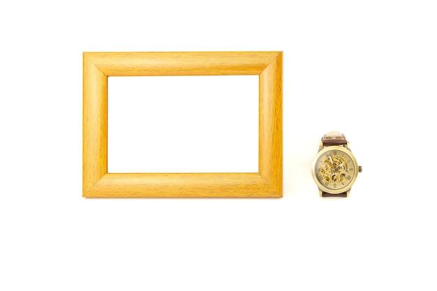 Portafoto in legno e orologio da polso meccanico isolato sul muro bianco.