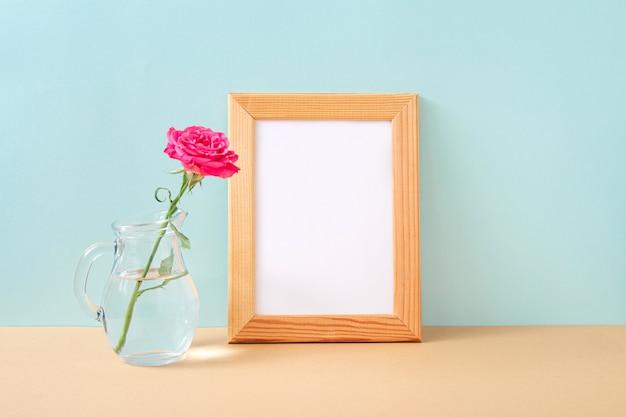 Cornice per foto in legno e rosa rosa in vaso di vetro su sfondo pastello. mock up con elementi decorativi. copia spazio