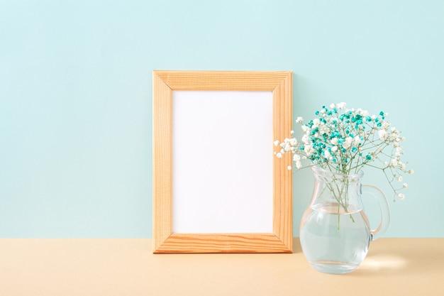 Cornice per foto in legno e piccoli fiori bianchi e blu in vaso su sfondo pastello. gypsophila fiori sullo scaffale o sulla scrivania. mock up con elementi decorativi. copia spazio.