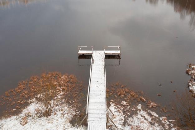 Molo in legno in riva al lago con anatre nel tardo autunno