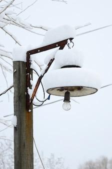 Una colonna di legno con una lampada a sospensione. il plafond della lampada è coperto da uno spesso strato di neve