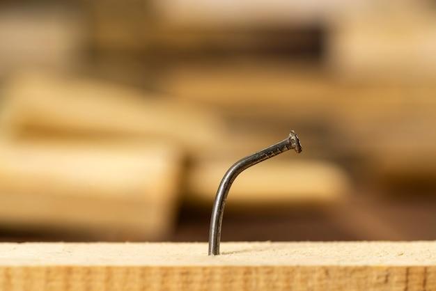 Tavola di legno con un chiodo piegato