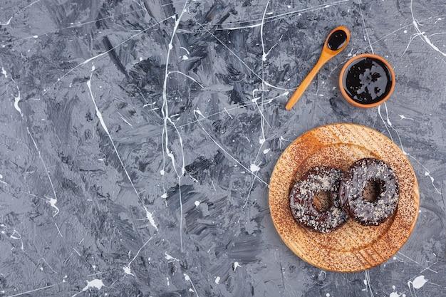Piatto di legno di ciambelle al cioccolato con granelli di cocco su sfondo marmo.