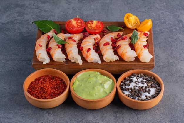 Un piatto di legno di deliziosi gamberetti con pomodorini a fette e pepe su uno sfondo di pietra. Foto Premium