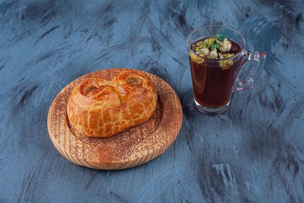 Piatto di legno di pasticceria fragrante fresca e tazza di tè sulla superficie di marmo.