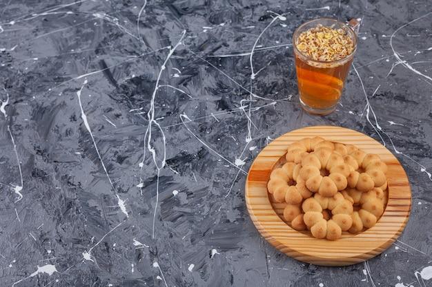 Piatto di legno di biscotti a forma di fiore dolce e tazza di tè su marmo.