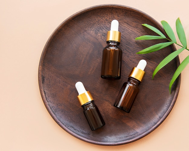 Piatto in legno con bottiglie di olio essenziale