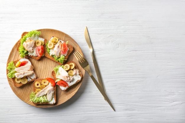 Piatto di legno con gustose bruschette di pollo sul tavolo