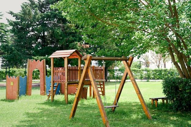 Parco giochi in legno con altalene su prato verde tra gli alberi