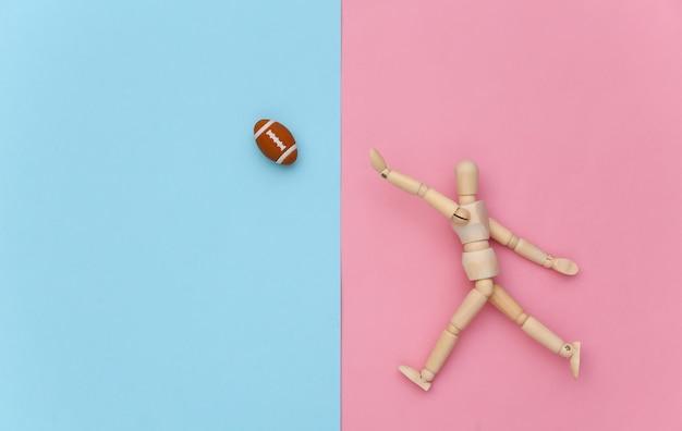 Burattino di legno che gioca a rugby con una palla su sfondo blu rosa