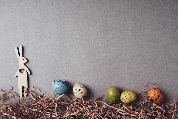 Coniglio di legno e uova di pasqua sull'erba, piatto, vista dall'alto, copia dello spazio. concetto di pasqua. decorazione festiva di pasqua su uno sfondo di carta grigia. sfondo luminoso in stile retrò. biglietto d'auguri.
