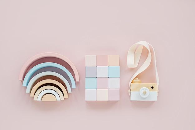 Arcobaleno in legno, blocchi colorati e macchina fotografica giocattolo. alla moda giocattoli per bambini su sfondo rosa pastello. accessori per giocattoli ecologici e privi di plastica per bambini. disposizione piatta, vista dall'alto