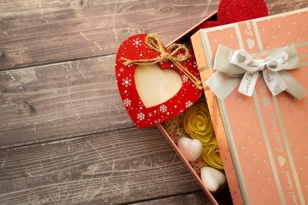 Cuore rosso in legno con posto per foto in una confezione regalo su uno sfondo di legno