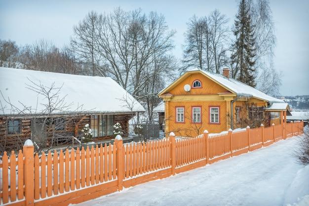 Residenziale in legno casa gialla e un recinto su nikolskaya street a plyos alla luce di una giornata invernale sotto un cielo blu